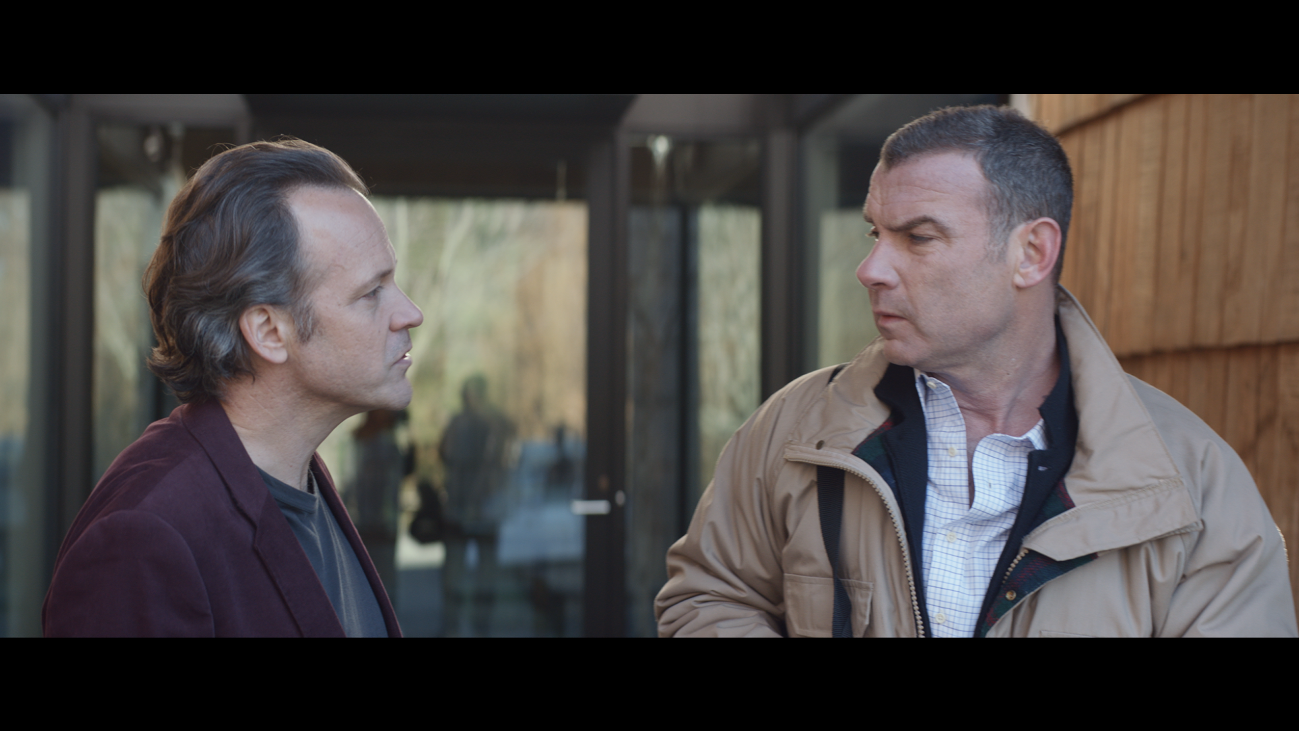 A still from the film, where two middle-aged white men face each other in front of a glass wall. One is frowning slightly and they look as if they are in the middle of a conversation.