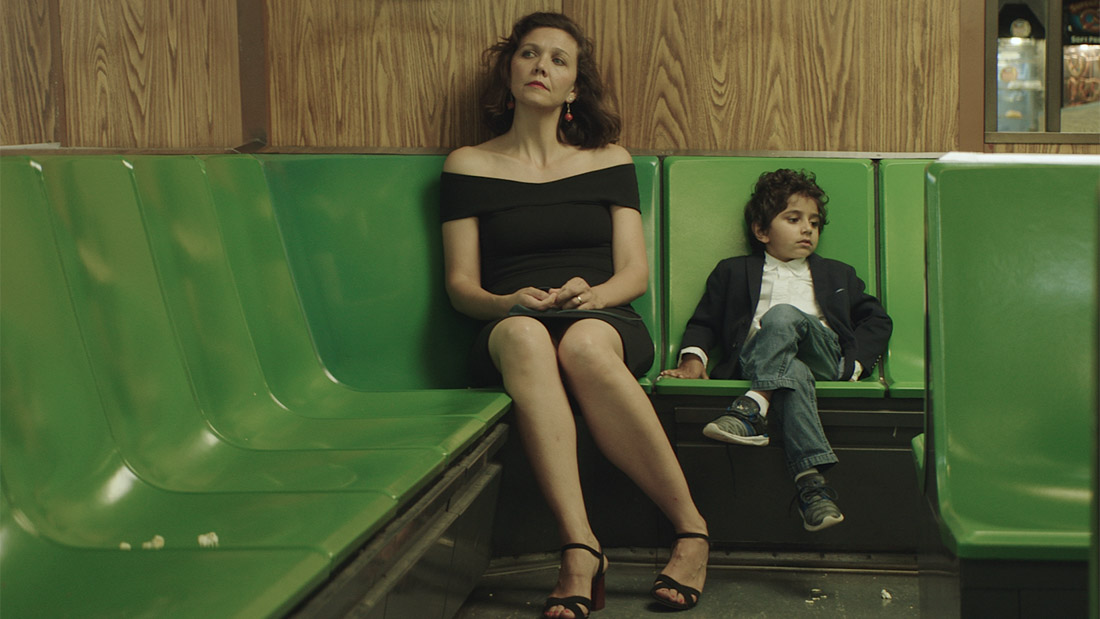 Maggie Gyllenhaal, a thin white woman with short dark hair and wearing a black dress, is looking into the distance to the left. A small child sitting next to her with his legs crossed, looking in the opposite direction. The chairs are green plastic and the walls are a medium-tone wood with prominent grain.